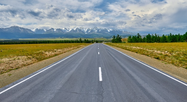 Highway stretching into the distance to the mountains with snowy peaks. altai