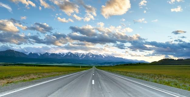 雪に覆われた山頂のある山々まで伸びる高速道路。アルタイ