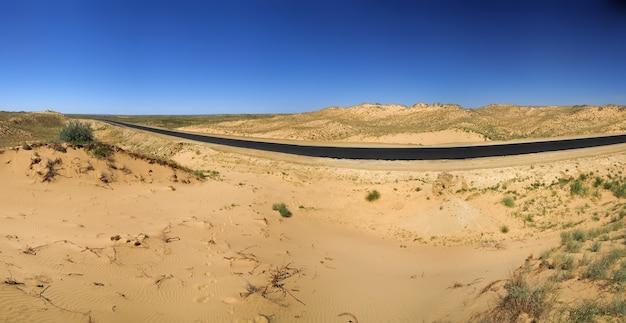 사막 아스팔트와 모래를 통과하는 고속도로