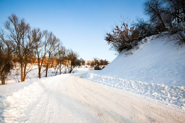 The highway in a winter season. the road is covered with snow