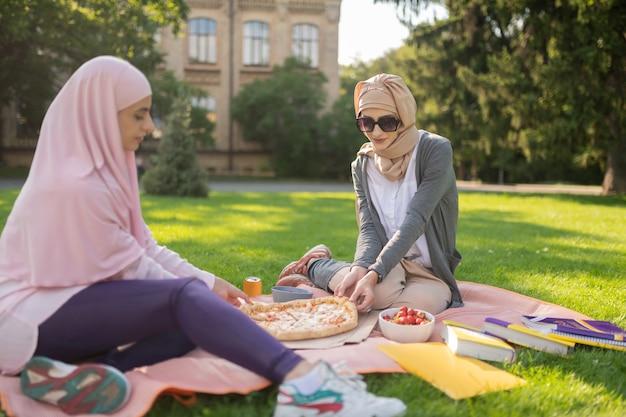 히잡과 선글라스. 피자를 먹으면서 밖에서 친구와 점심을 먹고 히잡과 선글라스를 착용 한 학생
