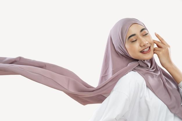 頬に手のジェスチャーで風に手を振る紫色のベールを身に着けて楽しんでいるヒジャーブの女の子