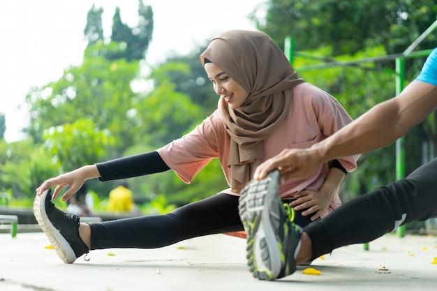 공원에서 운동하기 전에 다리 워밍업 운동을 함께하는 히잡 소녀