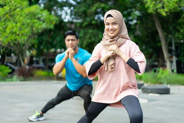 公園で運動する前に一緒に脚のウォームアップ運動をしているヒジャーブの女の子