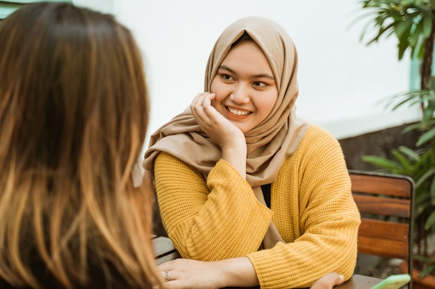 Hijab girls see friends while sitting chatting