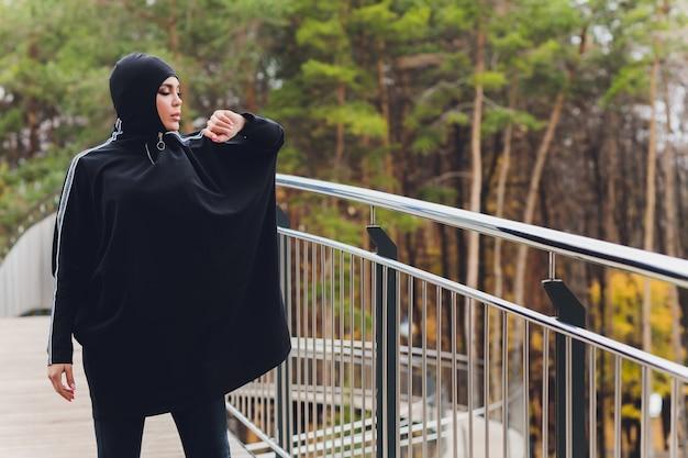 早朝に歩道橋にヒジャーブの女性