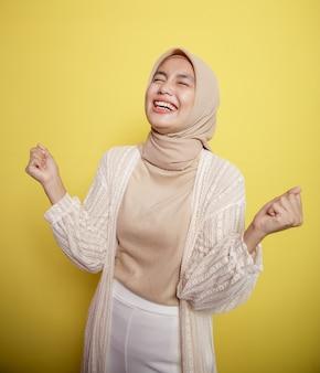 黄色の壁に孤立した非常に興奮したヒジャーブの女性
