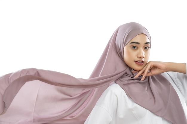 風になびく紫色のベールドレスを着たヒジャーブの女性