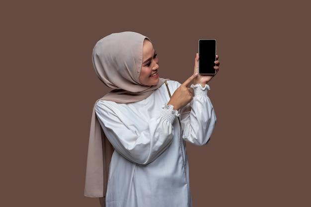 휴대폰을 들고 스크린 폰을 가리키는 히잡 여성