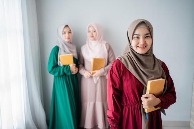 笑みを浮かべてヒジャーブ女性はアルコーランの神聖な本を保持します