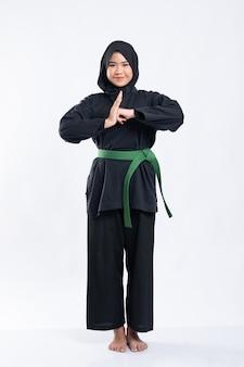 緑のベルトが付いたプンチャックシラットのユニフォームを着たヒジャーブの女性は、敬意を表する手のジェスチャーを実行します