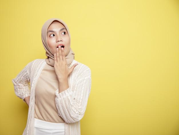 黄色の背景に分離されたショックを受けた表情のヒジャーブ女性