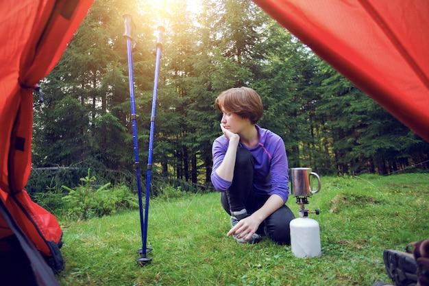 하이킹과 캠핑 생활. 관광 소녀의 텐트에서 보기는 버너에서 음식을 요리합니다