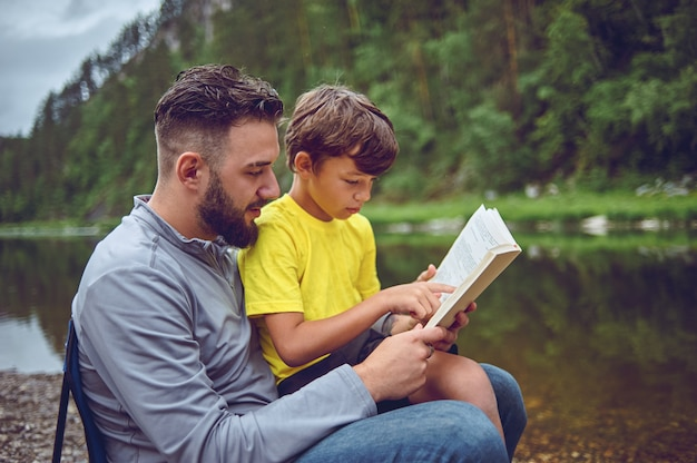 On a hike, on the river bank, father and son read a book