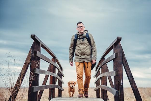 Hiker и собака на деревянном мосту
