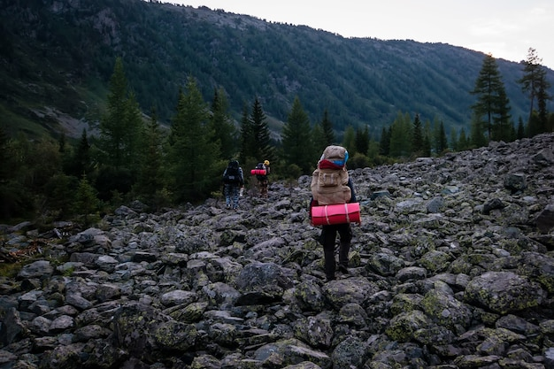山に登るハイカー。山腹の石の堆積物をこっそりと夜に大きなバックパックを持った観光客。
