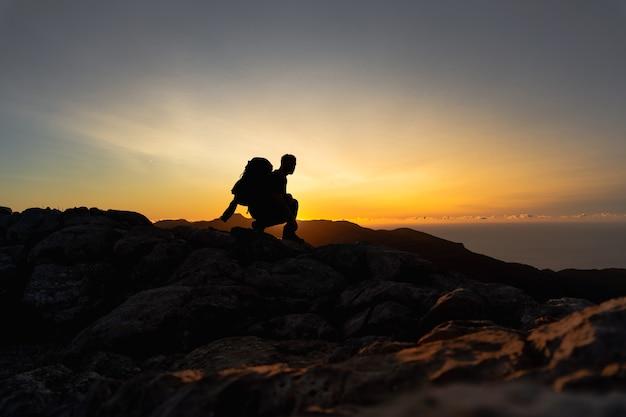 Путешественник на вершине горы, присев на корточки и наблюдая на горном хребте красивый золотой час, закат с интенсивным цветом и голубое небо, сливающееся с желтым человеком в профиль, смотрящим на солнце