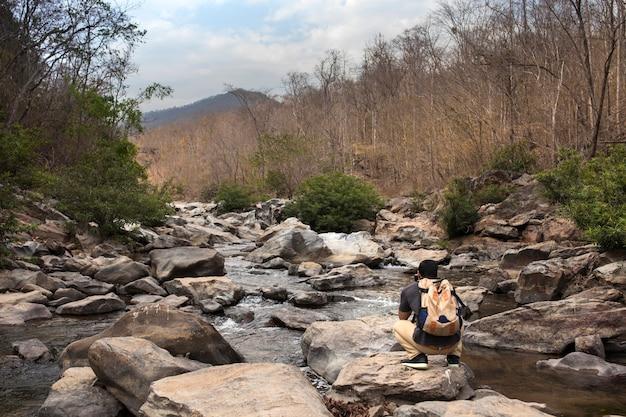 Escursionista chinandosi su pietra