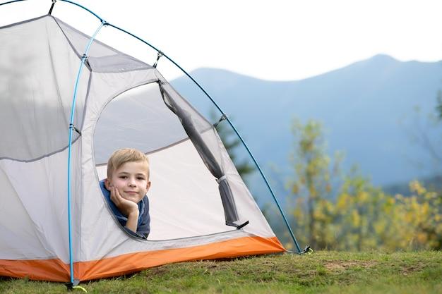 등산객 소년은 아름다운 여름 자연의 전망을 즐기는 산 캠프장의 관광 텐트에서 쉬고 있습니다.