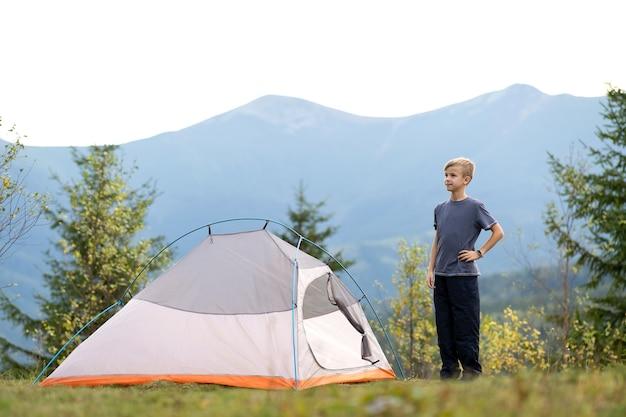 등산객 소년은 아름다운 여름 자연의 전망을 즐기는 산 캠프장에서 관광 텐트 근처에서 쉬고 있습니다.