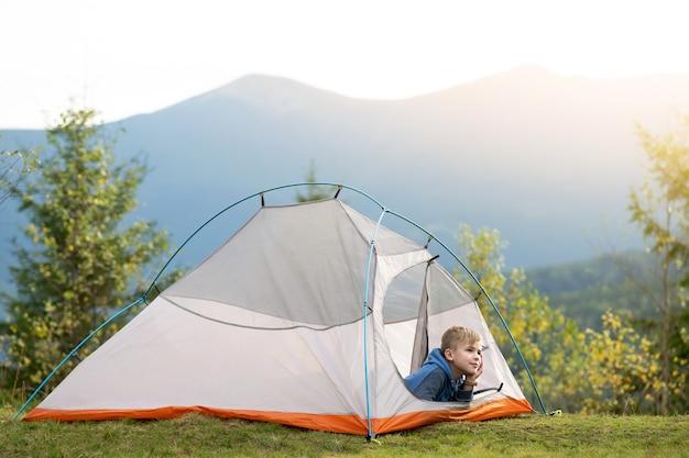 등산객 소년은 여름 자연의 전망을 즐기는 산 캠프장에서 캠핑 텐트에 앉아 쉬고 있습니다.