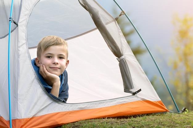 등산객 소년은 자연 경관을 즐기는 산 캠프장의 텐트 안에 앉아 있습니다.