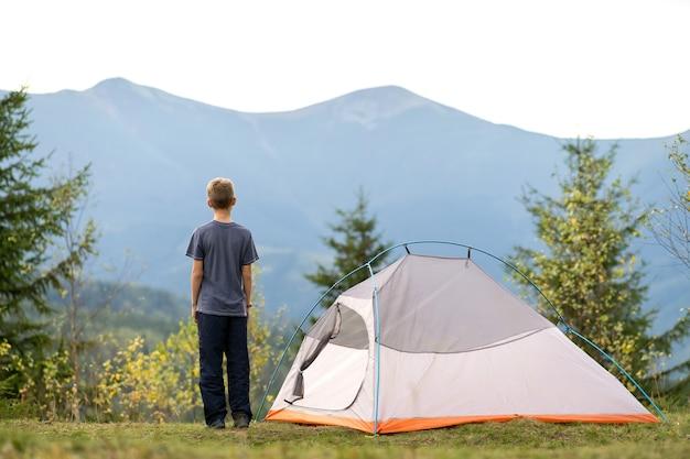 산 캠프장에서 텐트 근처에 서 있는 등산객 소년이 자연의 전망을 즐기고 있습니다.