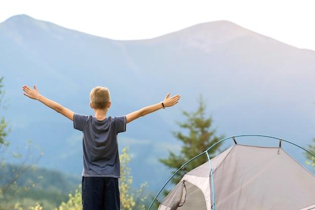 산 야영장의 텐트 근처에 서 있는 등산객 소년은 손을 들고 자연의 전망을 즐기고 있습니다.