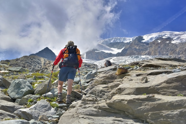 Hiker climbing rocky mountain and heading for snow-capped summit of a glacier