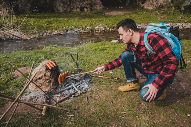Hiker cooking sausages
