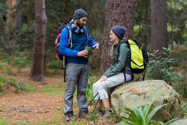 Hiker couple interacting with each other in forest