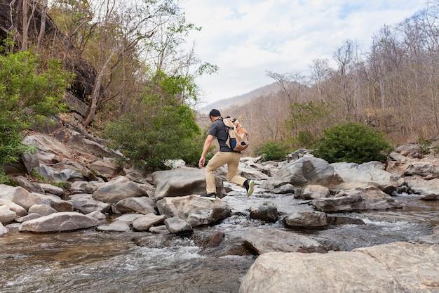 Hiker attraversa fiume selvaggio