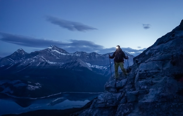 輝くヘッドランプのリムウォールサミットカナダで近くに山を下るハイカー