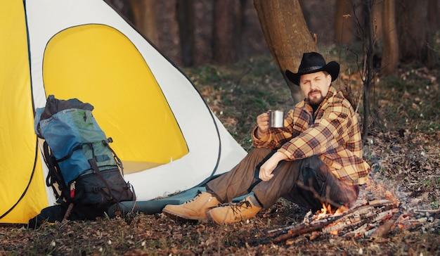 キャンプファイヤーの隣に座って熱いお茶を飲むハイカーと春の朝を楽しむ黄色と白のテント