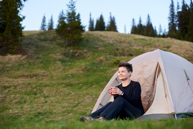 Турист пьет чай в палатке в горах