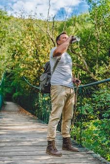 Hiker drinking water on the wooden suspension bridge