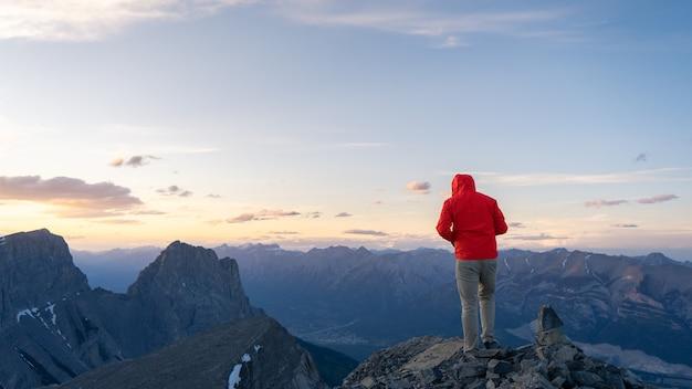 日没のリムウォールサミットカナダで山頂の景色を楽しむハイカー