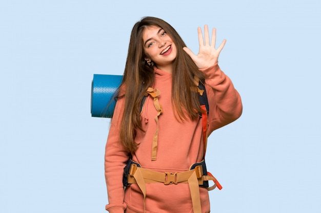 Hiker girl counting five with fingers on on blue