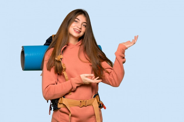 Hiker girl extending hands to the side for inviting to come on blue