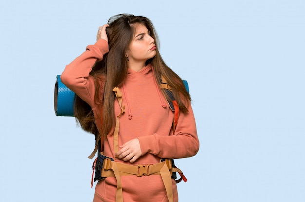 Hiker girl having doubts while scratching head on on blue