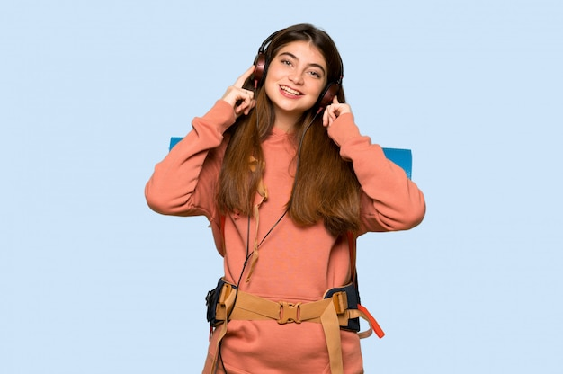 Hiker girl listening to music with headphones on blue