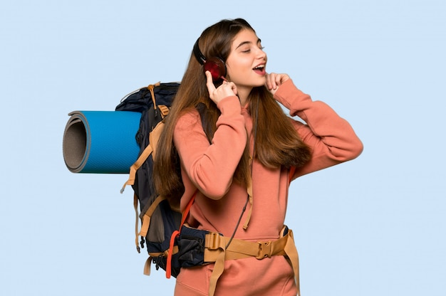 Hiker girl listening to music with headphones on on blue