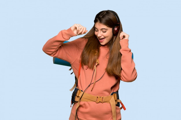Hiker girl listening to music with headphones and dancing on blue