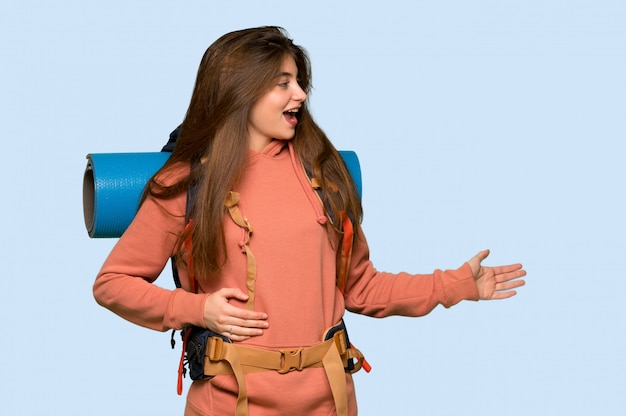 Hiker girl pointing back and presenting a product on blue