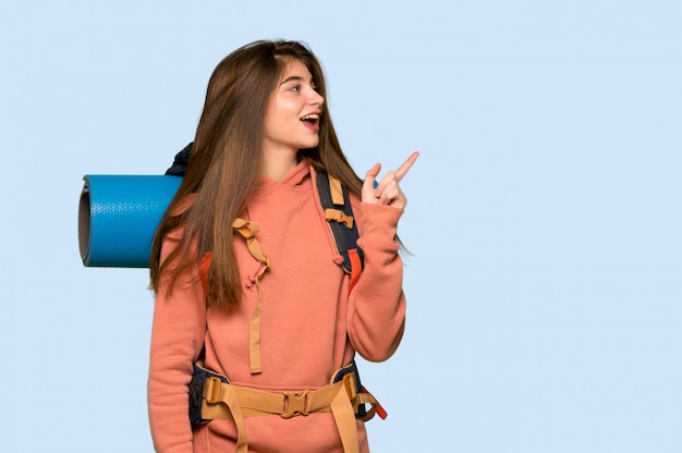 Hiker girl pointing finger to the side in lateral position on blue