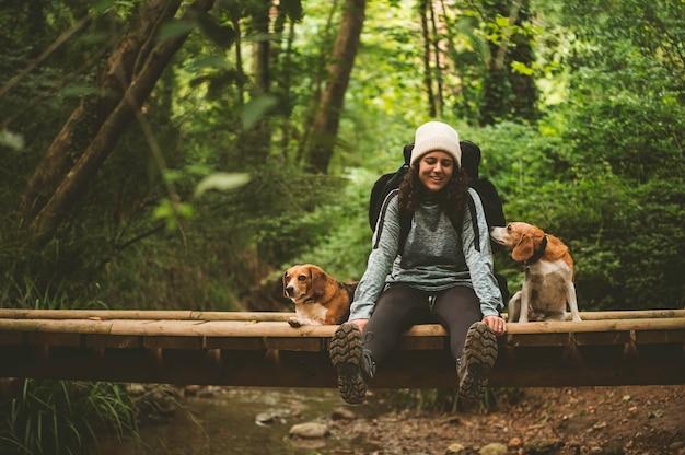 カメラを見て、犬と一緒に橋で休んでいるハイカーの女の子。