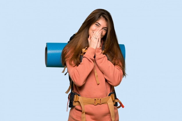 Hiker girl smiling a lot while covering mouth on blue background