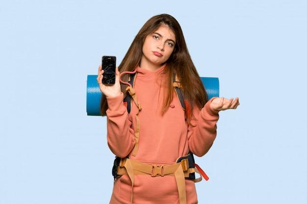 Hiker girl upset with a broken phone on blue