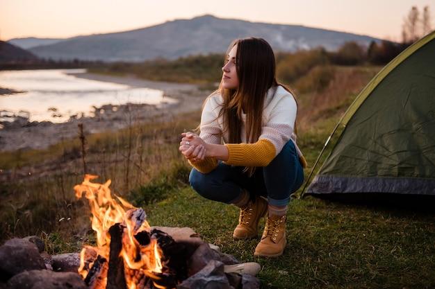 緑のテントの横で火のそばで体を温めるハイカーの女の子