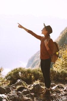 山の頂上にバックパックを持つハイカーの女の子秋のシーズン中に屋外で休暇を楽しんでいる女性
